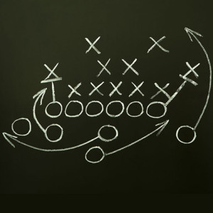 A chalk diagram of a football play on a chalkboard.