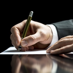 A formal looking photo of the hand of a business person in a suit signing a contract.